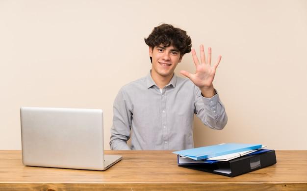 Junger studentenmann mit einem laptop, der fünf mit den fingern zählt