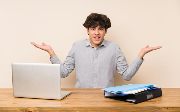 Junger studentenmann mit einem laptop mit entsetztem gesichtsausdruck