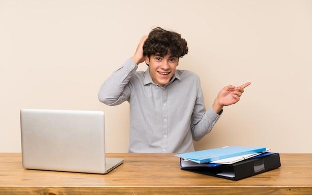 Junger studentenmann mit einem laptop überrascht und finger auf die seite zeigend