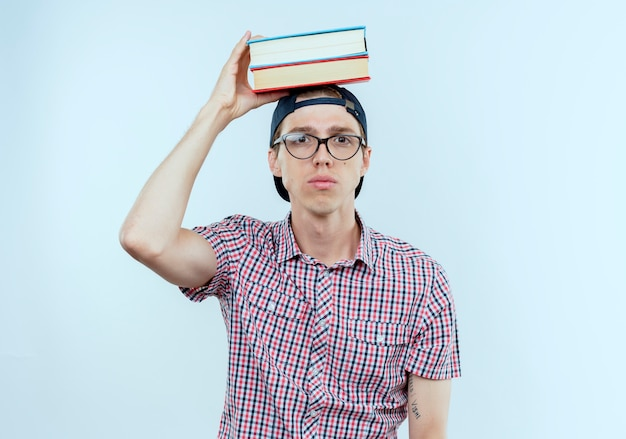 Junger studentjunge, der brille und kappe trägt, die bücher auf kopf setzen