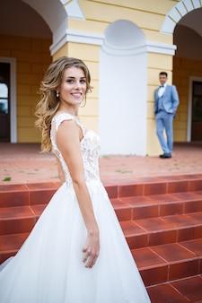 Junger stylischer kerl im kostüm des bräutigams und der braut schönes mädchen in einem weißen kleid mit einem zug, der auf dem hintergrund eines großen hauses mit säulen an ihrem hochzeitstag spaziert walking