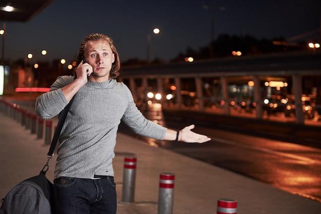 Junger stylischer mann, der durch den nachtbaum in der nähe der straße geht und ein gespräch am telefon führt