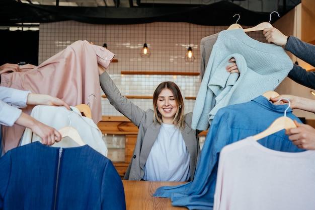 Junger stylist, der satz von hemden für modeschießen schaut