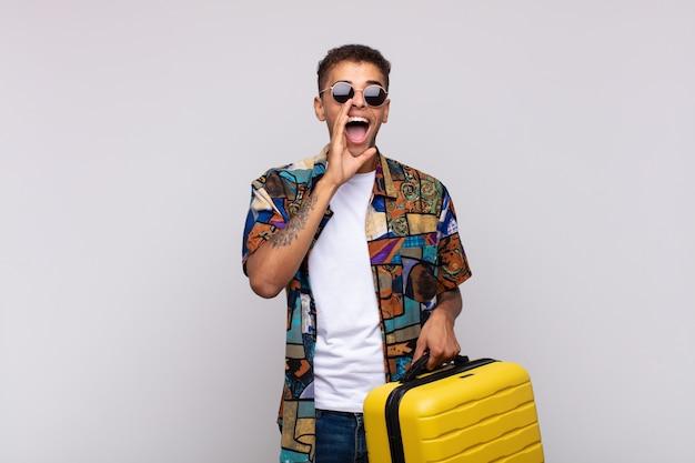 Junger südamerikanischer mann, der glücklich, aufgeregt und positiv fühlt, einen großen schrei mit den händen neben dem mund ausstößt und ruft