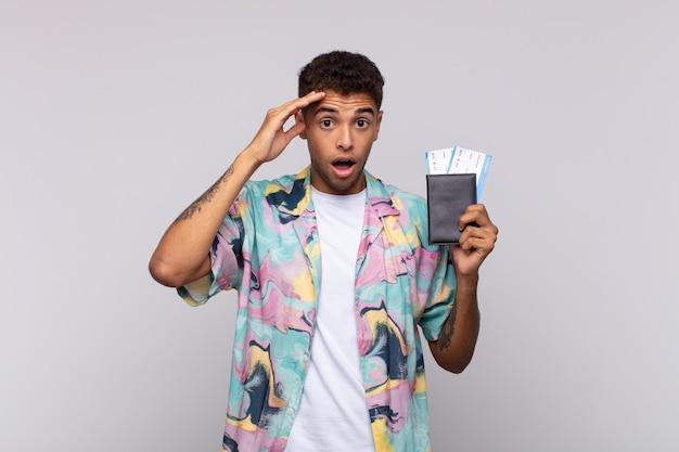 Junger südamerikanischer mann, der glücklich, erstaunt und überrascht aussieht, lächelt und erstaunliche und unglaubliche gute nachrichten realisiert