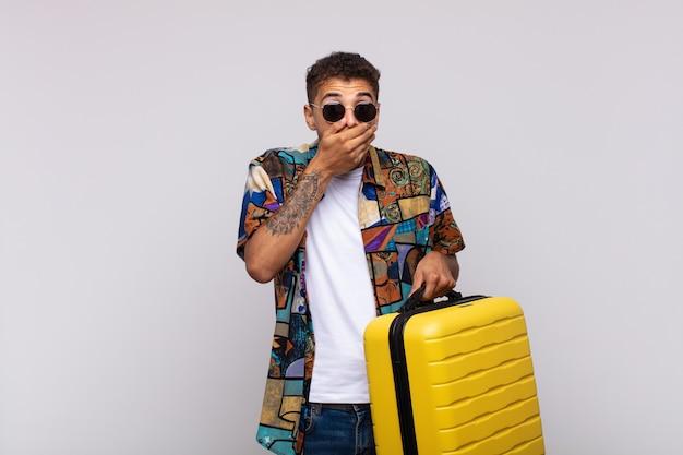 Junger südamerikanischer mann, der mund mit den händen mit einem schockierten, überraschten ausdruck bedeckt, ein geheimnis hält oder oops sagt
