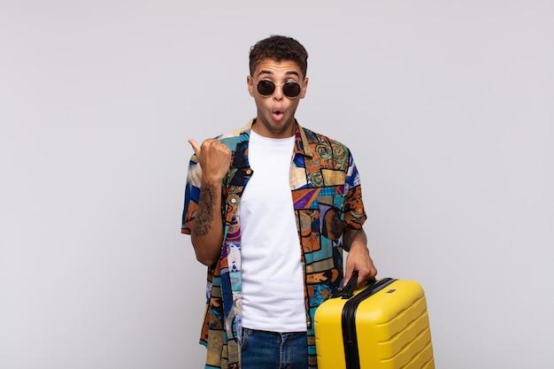 Junger südamerikanischer mann, der ungläubig erstaunt aussieht, auf objekt auf der seite zeigt und wow sagt, unglaublich