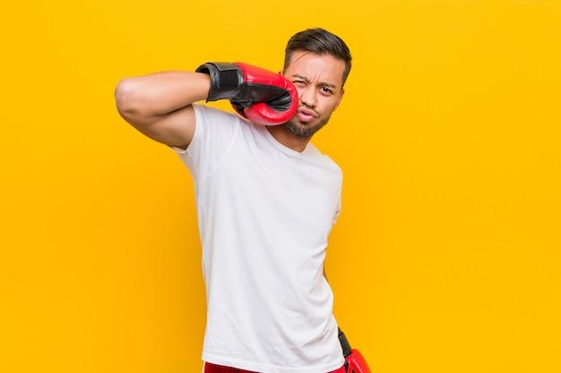 Junger südasiatischer boxermann, der rote handschuhe trägt.
