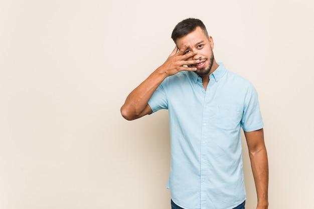 Junger südasiatischer mann blinzelt in die kamera durch finger, verlegenes bedeckungsgesicht.
