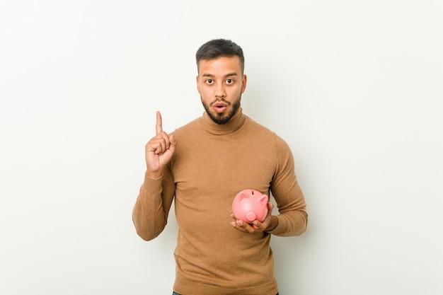 Junger südasiatischer mann, der ein sparschwein hält, das eine große idee hat