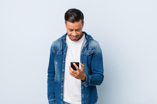 Junger südasiatischer mann, der ein telefon anhält