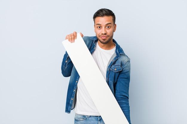 Junger südasiatischer mann, der ein weißes plakat hält.