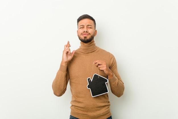 Junger südasiatischer mann, der eine hausikone hält, die finger für glück kreuzt