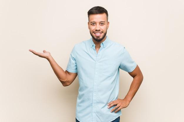 Junger südasiatischer mann, der eine leere stelle auf einer handfläche zeigt und eine andere hand auf taille hält.