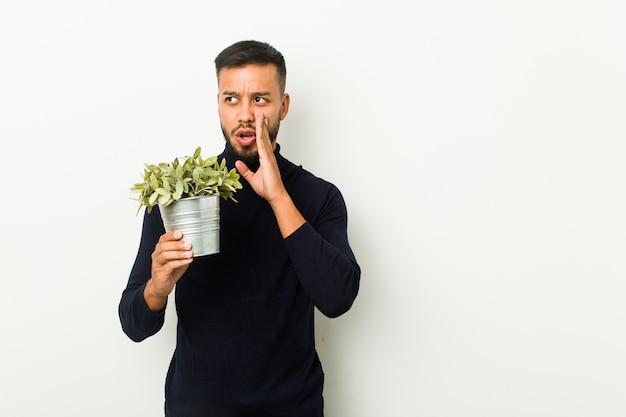 Junger südasiatischer mann, der eine pflanze hält, sagt eine geheime heiße bremsnachricht und schaut zur seite