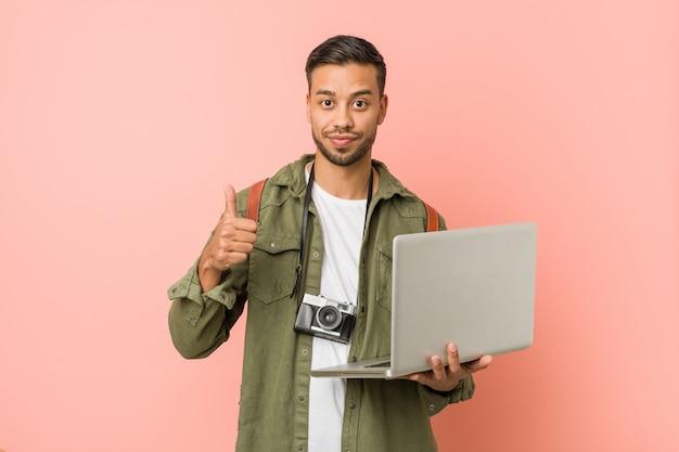 Junger südasiatischer mann, der einen laptop anhält.