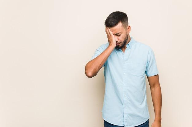 Junger südasiatischer mann, der etwas vergisst, stirn mit palme schlägt und augen schließt.