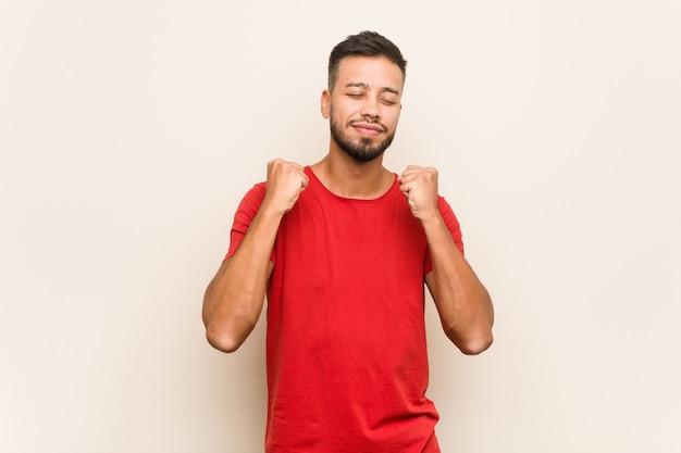 Junger südasiatischer mann, der faust anhebt, glücklich und erfolgreich sich fühlt. sieg-konzept.