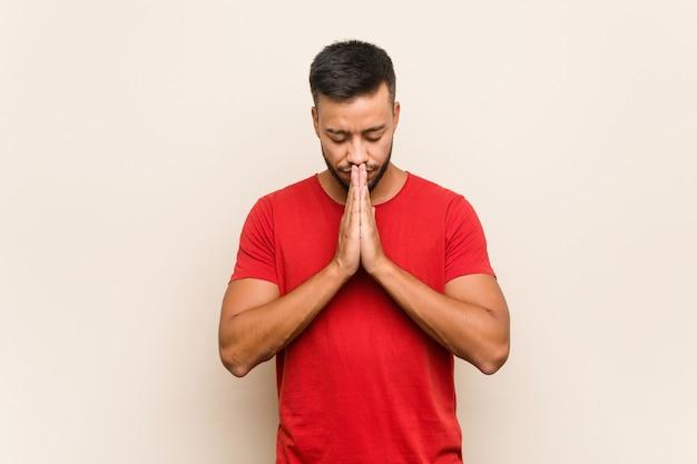 Junger südasiatischer mann, der hände im gebet nahe mund hält, fühlt sich zuversichtlich.