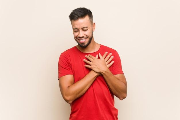 Junger südasiatischer mann, der lachend hände auf herz hält, konzept des glücks.