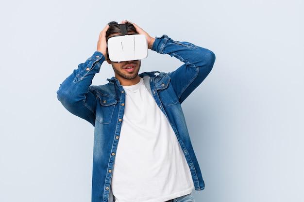 Junger südasiatischer mann, der mit gläsern der virtuellen realität spielt