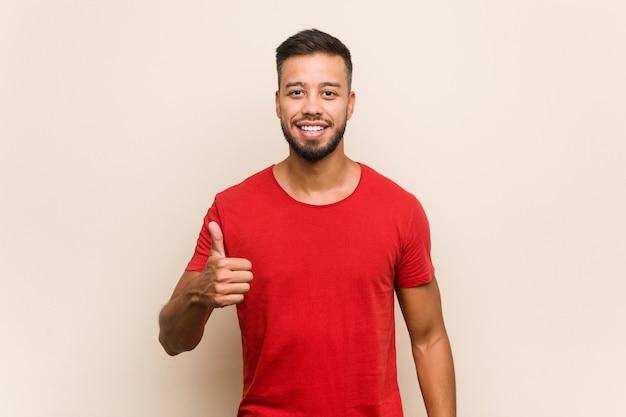 Junger südasiatischer mann, der oben daumen lächelt und anhebt