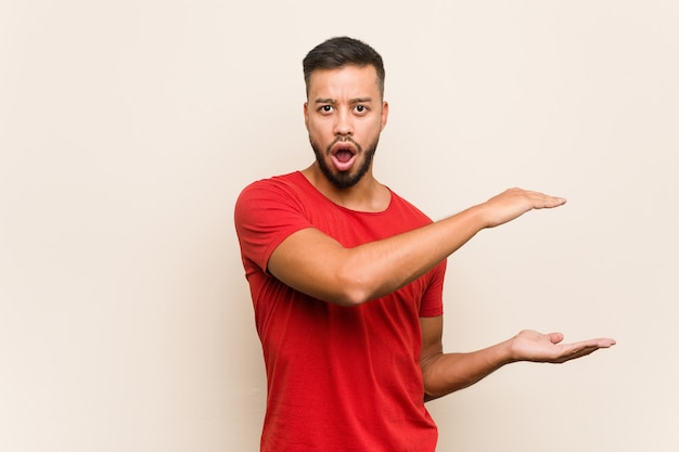 Junger südasiatischer mann entsetzt und überrascht, einen kopienraum zwischen händen halten.