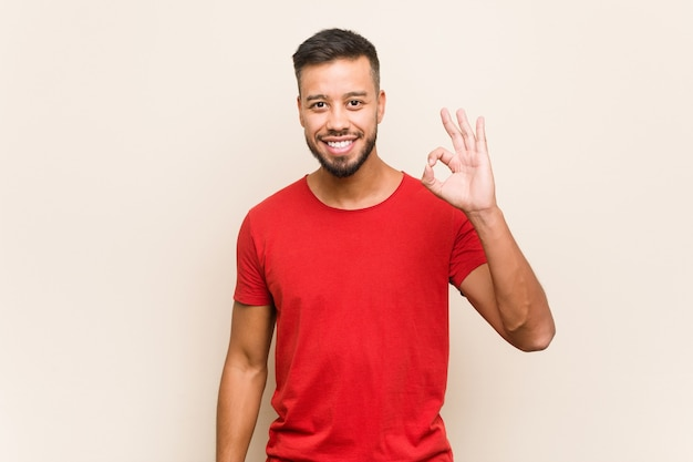 Junger südasiatischer mann fröhlich und zuversichtlich, ok geste zeigend.