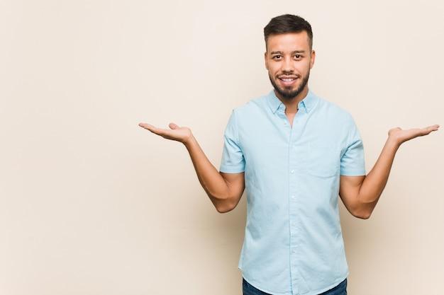 Junger südasiatischer mann macht skala mit den armen, fühlt sich glücklich und überzeugt.