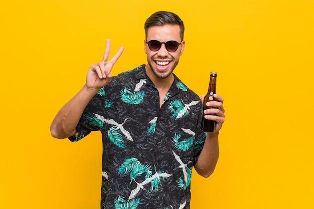 Junger südasiatischer reisender, der eine bierflasche hält.