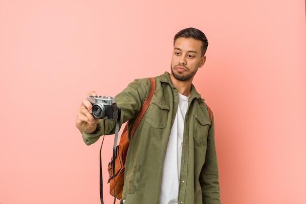 Junger südasiatischer reisender, der fotos mit einer retro- kamera macht.