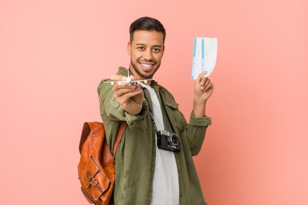 Junger südasiatischer reisender, halten flugtickets.