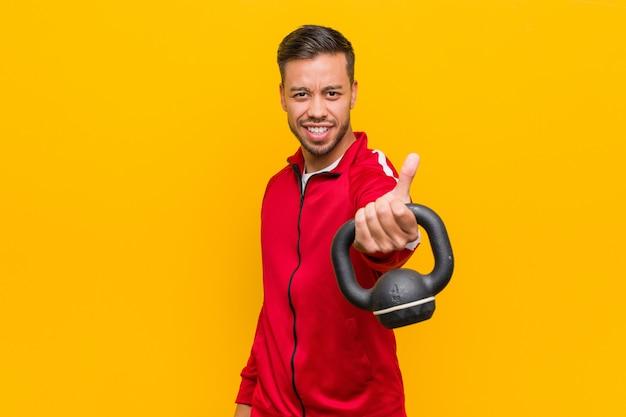 Junger südasiatischer sportmann, der einen dummkopf hält