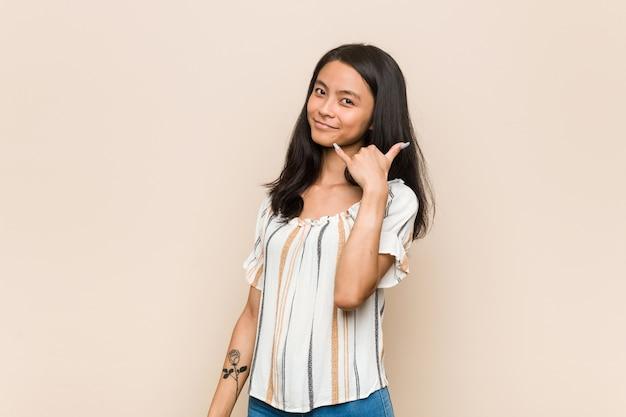 Junger süßer chinesischer teenager junge blonde frau, die einen mantel auf rosa hintergrund trägt, der eine handy-anrufgeste mit den fingern zeigt.
