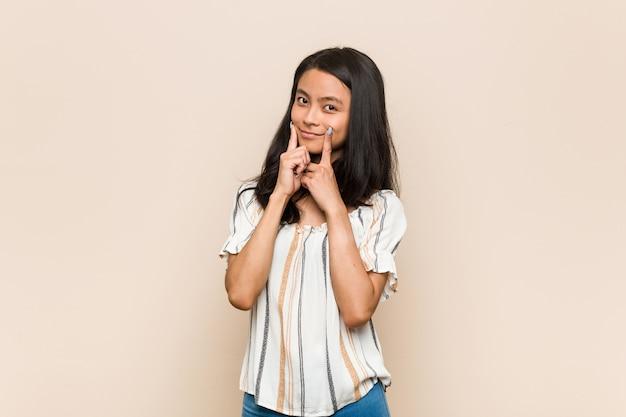 Junger süßer chinesischer teenager junge blonde frau, die einen mantel auf rosa zweifel zwischen zwei optionen trägt.
