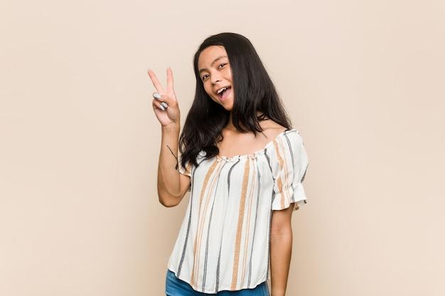 Junger süßer chinesischer teenager junge blonde frau, die einen mantel gegen einen rosa hintergrund freudig und sorglos zeigt ein friedenssymbol mit den fingern zeigend.