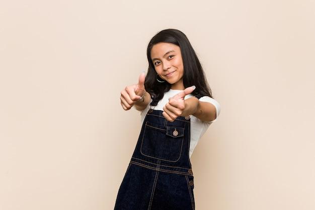Junger süßer chinesischer teenager junge blonde frau, die einen mantel gegen einen rosa hintergrund mit daumen hoch trägt, jubel über etwas, unterstützung und respektkonzept.