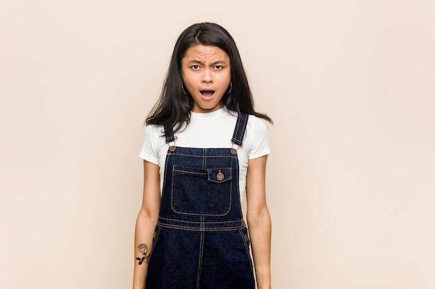Junger süßer chinesischer teenager junge blonde frau, die einen mantel gegen einen rosa hintergrund trägt, der sehr wütend und aggressiv schreit.