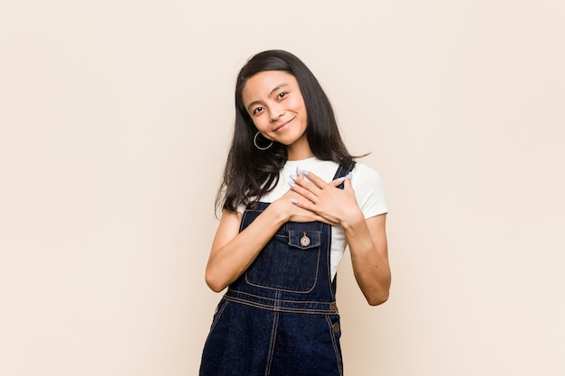 Junger süßer chinesischer teenager junge blonde frau, die einen mantel vor einem rosa hintergrund trägt, hat freundlichen ausdruck, der handfläche zur brust drückt. liebeskonzept.