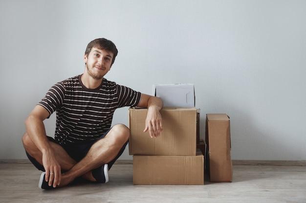 Junger süßer kerl sitzt auf dem boden in einer neuen wohnung nach der reparatur zwischen den pappkartons, glücklich und lächelnd.
