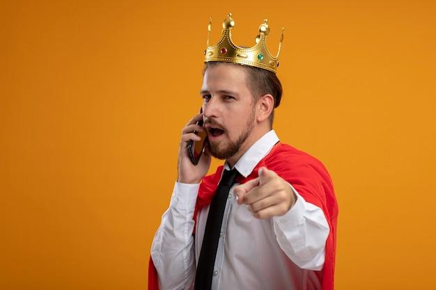 Junger superheld, der krawatte und krone trägt, die kamera betrachten, spricht am telefon, das sie geste lokalisiert auf orange hintergrund zeigt