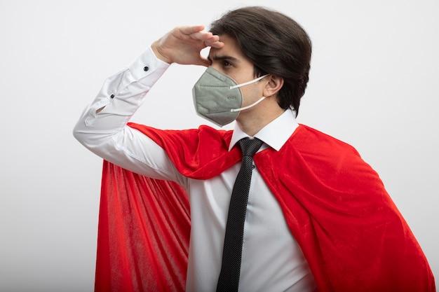 Junger superheld, der krawatte und medizinische maske trägt, die entfernung mit hand lokalisiert auf weiß betrachtet