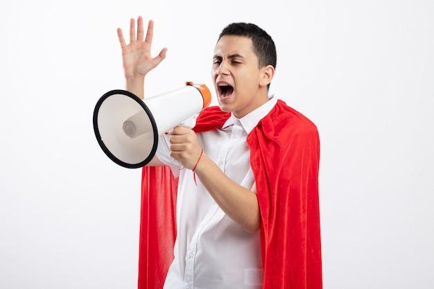 Junger superheldenjunge im roten umhang, der in der profilansicht steht und gerade schreit in lautsprecherlautsprecher hochhebt, lokalisiert auf weißem hintergrund mit kopienraum