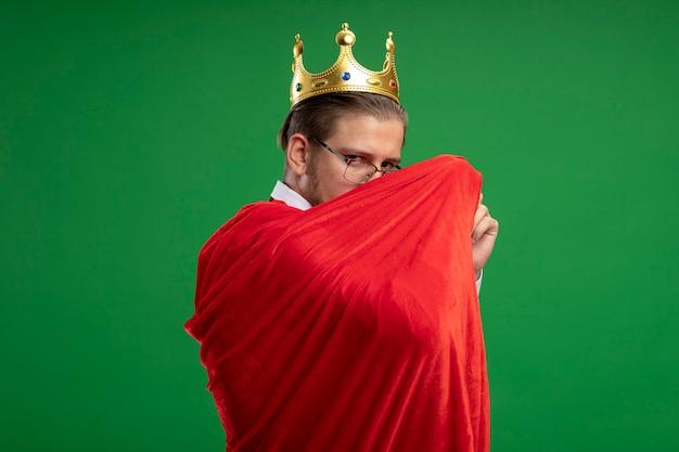 Junger superheldenmann, der krone und krawatte trägt, die in umhang eingewickelt lokalisiert auf grün