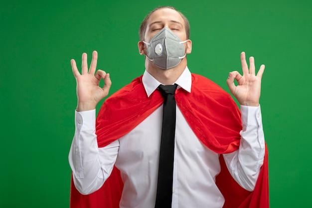 Junger superheldenmann, der medizinische maske und krawatte mit geschlossenen augen trägt, die meditation lokalisiert auf grünem hintergrund tun