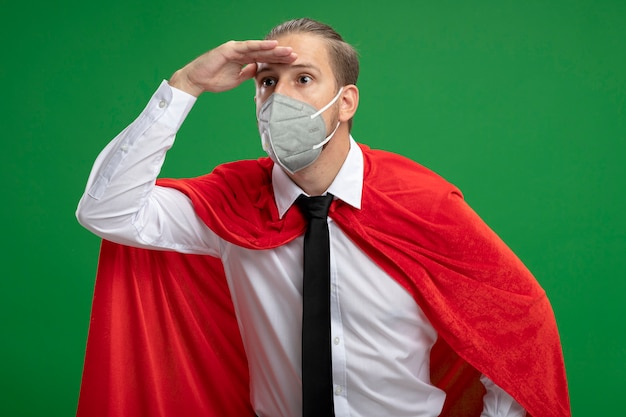 Junger superheldenmann, der medizinische maske und krawatte trägt, die entfernung mit hand lokalisiert auf grün betrachtet