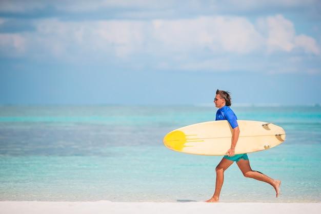 Junger surfer am weißen strand mit gelbem surfbrett
