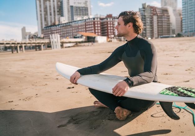 Junger surfer, der auf sandstrand sitzt und den ozean mit seinem surfbrett betrachtet. sport- und wassersportkonzept.