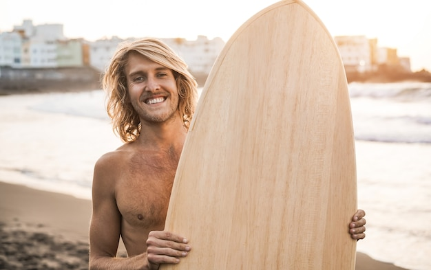 Junger surfer, der bei sommersonnenuntergang surfbrett am strand hält