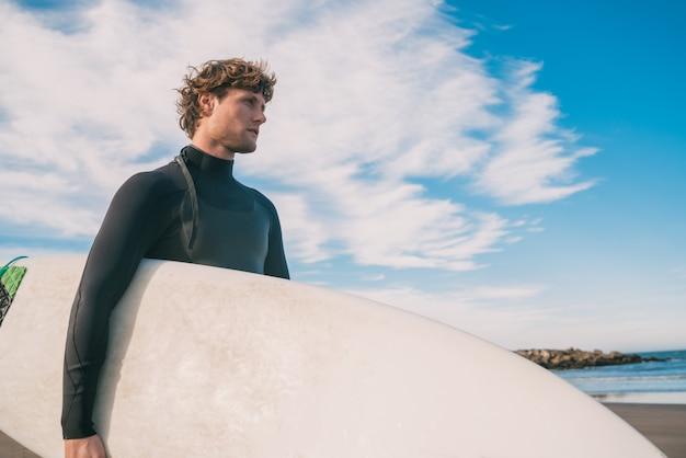 Junger surfer, der im meer mit seinem surfbrett in einem schwarzen surfanzug steht. sport- und wassersportkonzept.